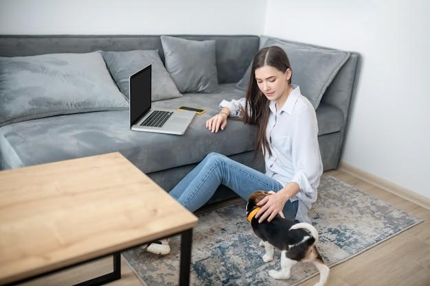 自宅で仕事をしている女性、隣で遊んでいる子犬
