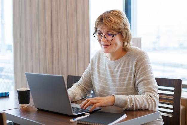 Женщина работает за ноутбуком в офисе на рабочем месте. она читает на компьютере и улыбается в кафе.