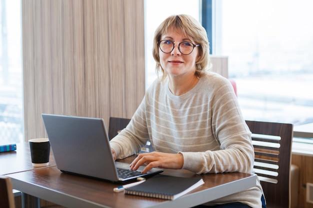Женщина работает за ноутбуком в офисе на рабочем месте. она читает на компьютере.