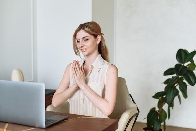 女性が自宅で仕事をし、同僚との会議でコミュニケーションをとる