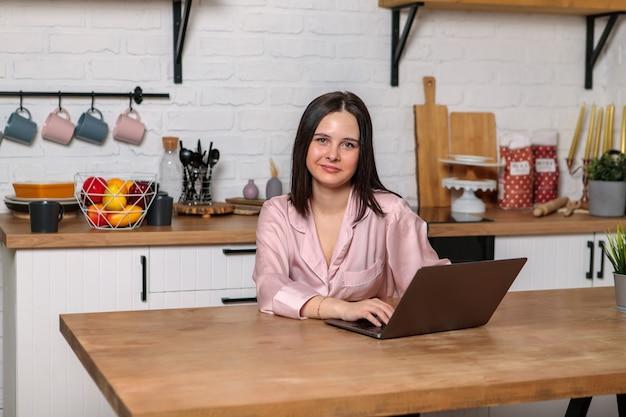 Женщина работает в офисе удаленно из дома на кухне, сидя за компьютером. дистанционное обучение онлайн, обучение и работа. студентка готовится к экзаменам.