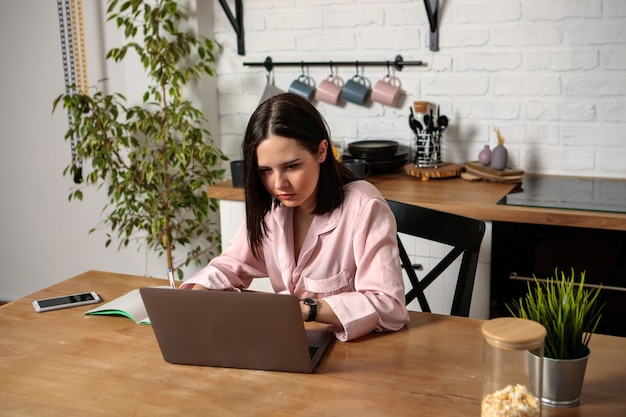 한 여성이 집에서 부엌에있는 사무실에서 컴퓨터 앞에 앉아 원격으로 일합니다. 원격 교육 온라인 교육 및 업무. 여자 학생은 시험을 준비합니다.
