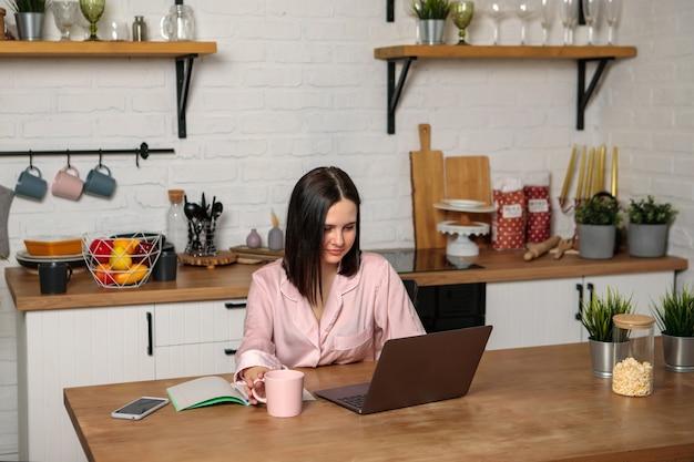 女性は、自宅から離れたオフィスのキッチンで、コンピューターの前に座って働いています。遠隔教育オンライン教育と仕事。女子学生は試験の準備をします。