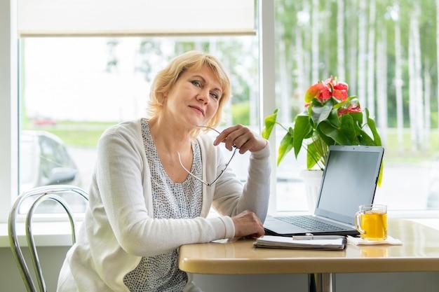 한 여성이 카페 테이블에서 노트북으로 일하고 있습니다. 중년 여성, 사무실에서 일하는 비즈니스 우먼. 그녀는 이메일, 소셜 미디어를 봅니다.