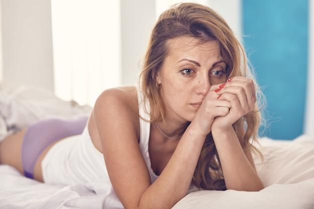 朝、ベッドで何か心配している女性