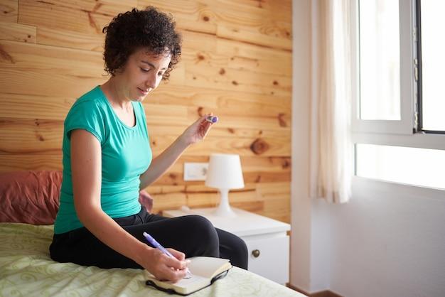 女性は自分のノートに基礎体温計で取った温度を書き留めます