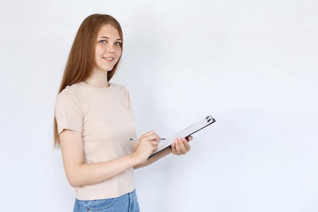 女性は白い背景の上のタブレットに書き込みます。テキスト用のスペース