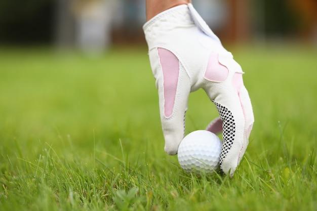 여자 장갑을 낀 손은 골프공을 골프 코스의 밝은 육즙 잔디에 놓습니다