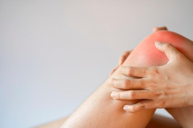 무릎 또는 뼈 통증 건강 관리 및 의학 개념으로 무릎 부위를 잡고 있는 여성의 손