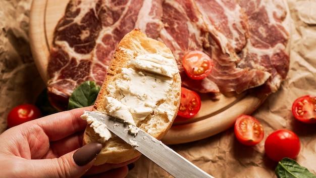 여자의 손에 브루스케타를 들고 칼로 두부 치즈를 펼칩니다.