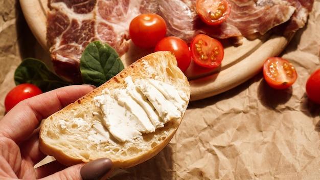 여자의 손에 브루스케타를 들고 두부 치즈를 펼칩니다.