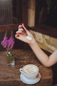 女性の手は、コーヒーからのミルクフォームのスプーン、アスティルベのピンクの花と緑の葉の小枝が付いたガラスの花瓶のある木製のテーブルの上に立つカップを持っています。
