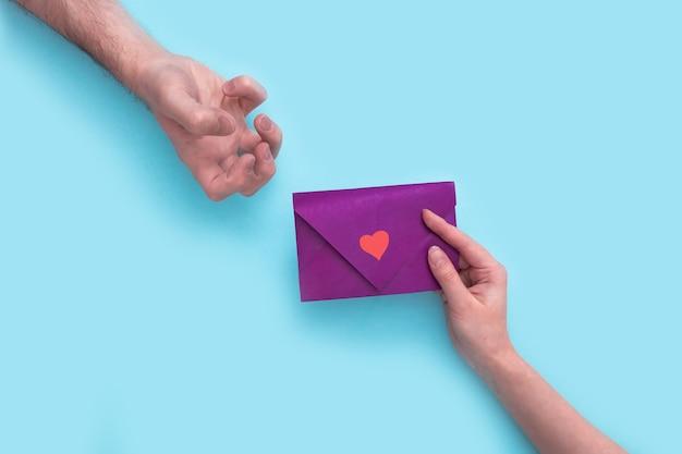 여자의 손은 발렌타인 데이에 보라색 봉투를 들고 남자 손에 표현하는