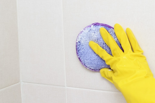 黄色い手袋をはめた女性の手が洗剤でバスルームのタイルを掃除する家を掃除する