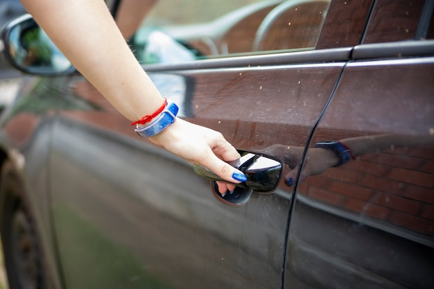 女性の手が黒い車の運転席のドアを開ける