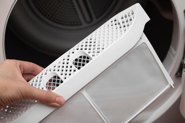 여자의 손이 기계 사용 후 건조기의 더러운 공기 필터에서 보풀을 제거하는 의류 건조기 용 다운 필터의 건조기 필터를 꺼냅니다.