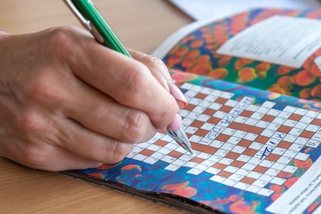 Женская рука с ручкой пишет решения кроссворда, крупным планом, концепцию тренировки разума