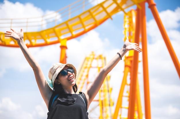 У женщин веселый счастливый день радости в парке развлечений в солнечный летний день, американские горки, прыгающая девушка, отпуск, отдых, концепция мероприятий. азиатские женщины, красивое ясное голубое небо. наслаждайся моментом