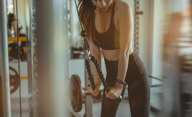 ダンベルで筋肉をポンピングして体重を増やしているジムでトレーニングアームを働いている女性