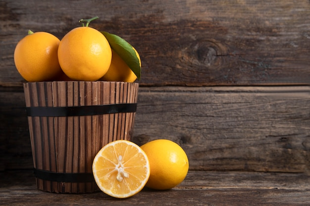 木製のテーブルの上に置かれた葉と新鮮なレモンの果実でいっぱいの木製のバスケット。高品質の写真