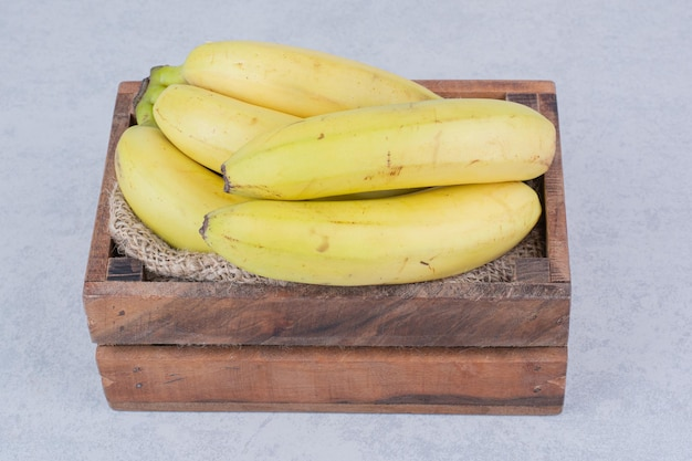 Деревянная корзина, полная спелых фруктовых бананов на белом фоне. фото высокого качества