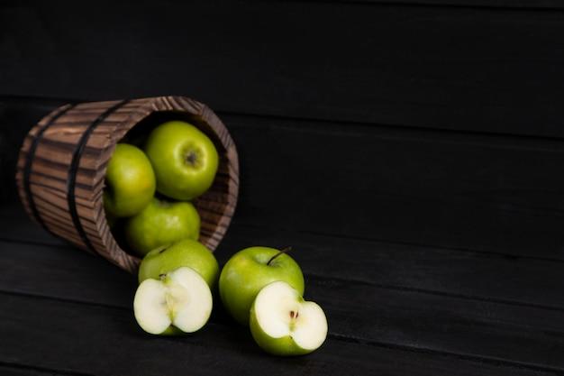 익은 녹색 사과 가득한 나무 바구니는 어두운 나무 테이블에 배치됩니다. 고품질 사진