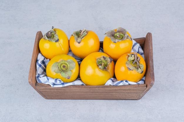 白い背景の上の甘い柿でいっぱいの木製バスケット。高品質の写真