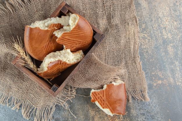 荒布の上に甘いおいしいペストリーの木製バスケット