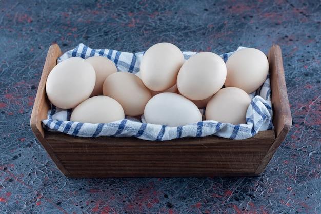 Деревянная корзина со свежими сырыми куриными яйцами