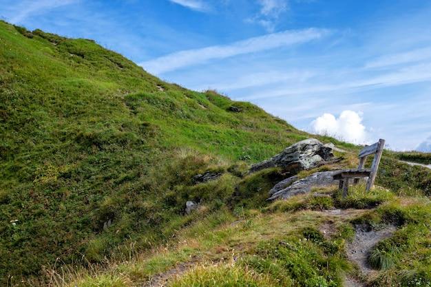 Деревянная скамейка на вершине альп, место для туристов, чтобы расслабиться и посмотреть на красивые пейзажи.