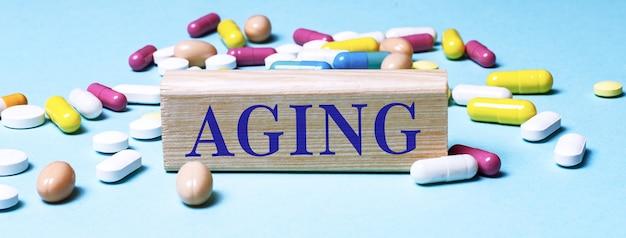 Деревянный блок со словом старение стоит на синем фоне среди разноцветных таблеток.