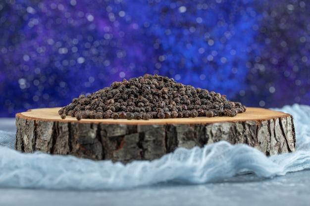 Деревянная доска, полная сушеных горошин перца.