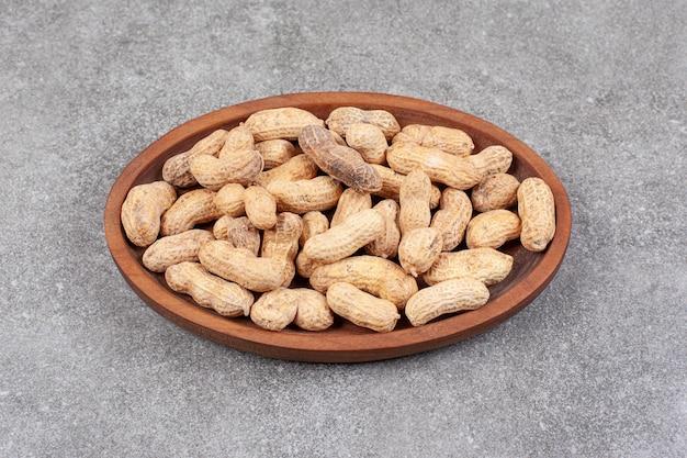 殻付きの健康的なピーナッツでいっぱいの木の板