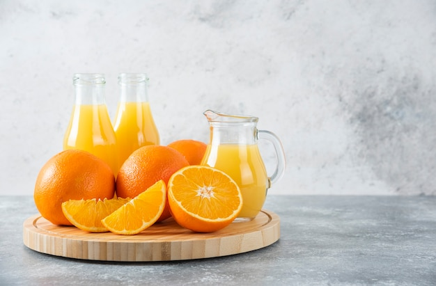 돌 테이블에 오렌지 과일의 육즙 조각으로 가득한 나무 보드.