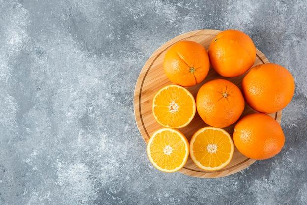 Деревянная доска, полная сочных ломтиков апельсина на каменном столе.