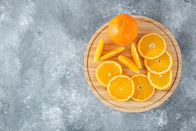 石のテーブルにオレンジ色の果物のジューシーなスライスでいっぱいの木の板。