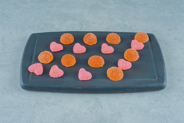 Деревянная доска, полная апельсиновых сладких желейных конфет с желейными конфетами в форме сердца
