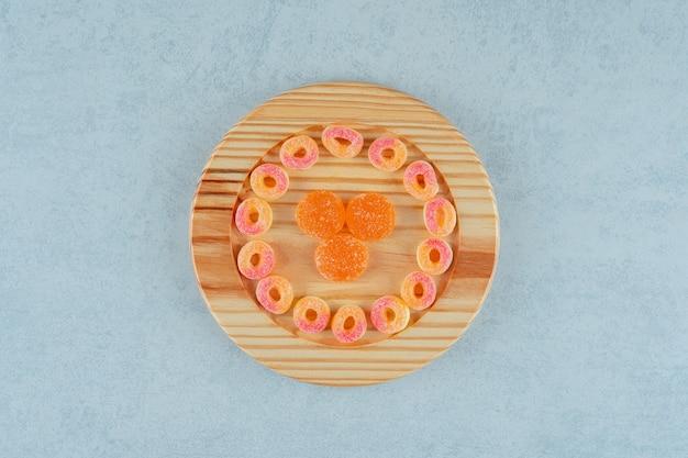 고리 모양의 둥근 오렌지 마멀레이드와 설탕이 든 오렌지 젤리 캔디로 가득한 나무 판자. 고품질 사진