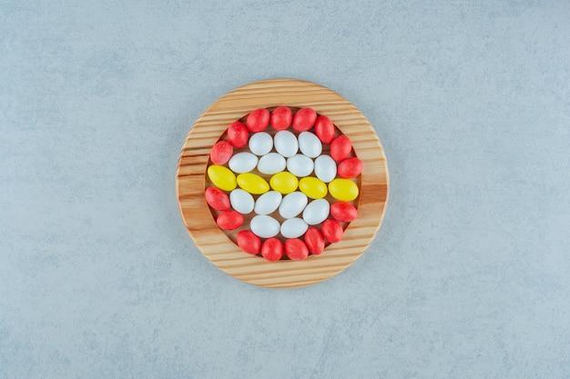 白い背景の上の丸い甘いカラフルなキャンディーでいっぱいの木の板。高品質の写真