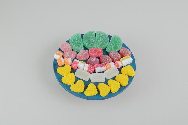 Деревянная доска, полная сладких желейных конфет.