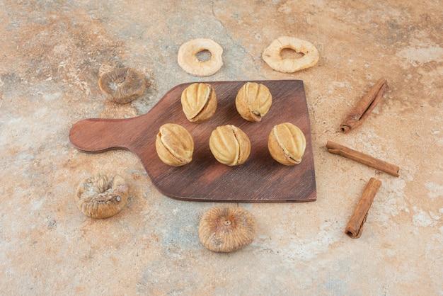 Деревянная доска, полная сладкого печенья и палочек корицы