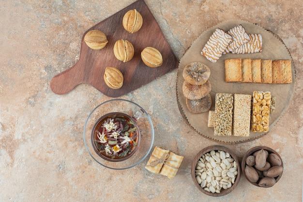 Деревянная доска, полная сладкого печенья и чашка травяного чая
