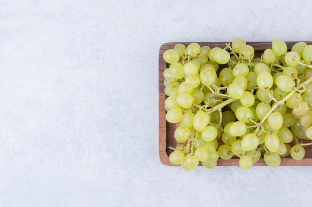 白い背景の上の甘いブドウでいっぱいの木の板。高品質の写真