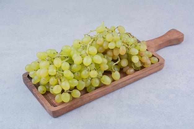 Деревянная доска, полная сладкого винограда на белом фоне. фото высокого качества