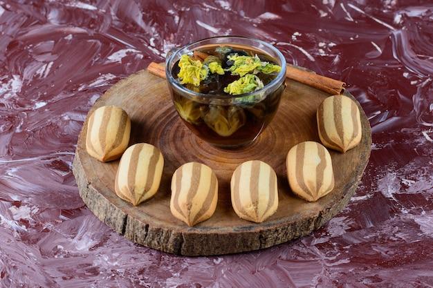 ハーブの熱いお茶のガラスカップと甘い縞模様のクッキーでいっぱいの木の板