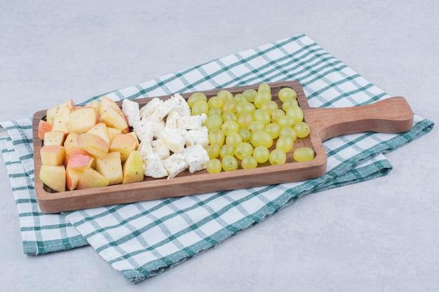 ホワイトチーズとスライスしたフルーツがたっぷり入った木の板。高品質の写真