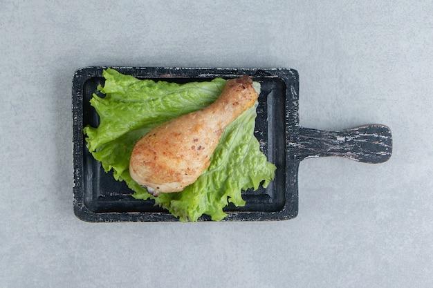 Деревянная доска жареной куриной ножки с салатом.