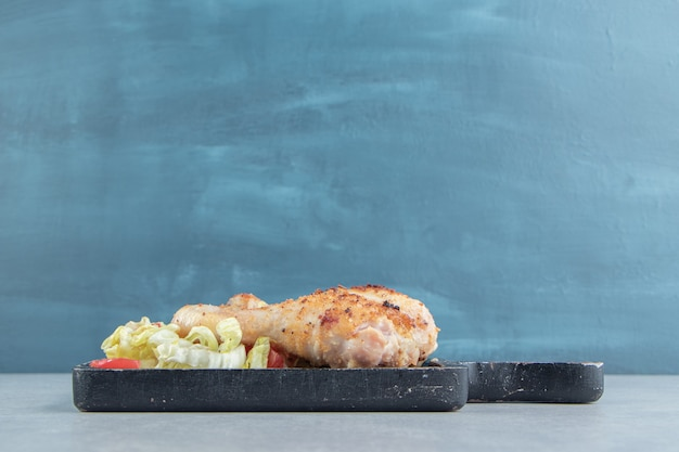 Деревянная доска из куриного жареного мяса с салатом.