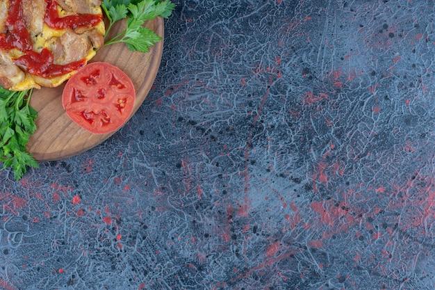 肉と野菜が入った美味しいオムレツの木板。