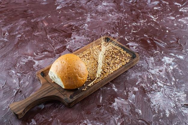 Деревянная доска свежей белой булочки с колосом пшеницы на светлом фоне.